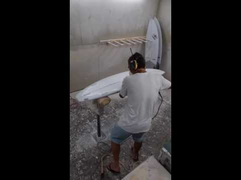 Grinding a surfboard lap before a bottom hotcoat.