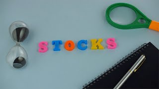 "Pan shot of the word ""Stocks"" composed with colorful letters on a blue platform"