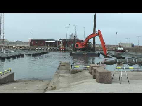 Volvo loader pulls up large deck at the dock  Hitachi excavator dredge in Visby harbor where the boa