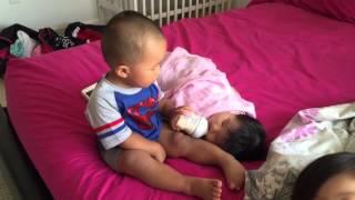 Toddler bottle feeding baby