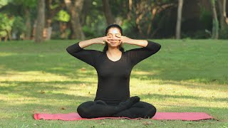 A young girl practicing bhramari / bee breathing pranayama outside in a park