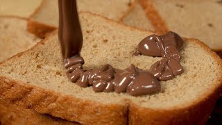 Close up shot of choco spread falling on a brown bread in a beautiful pattern