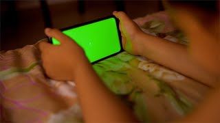 Young Indian child watching cartoon movie on a mobile phone, green screen - technology concept