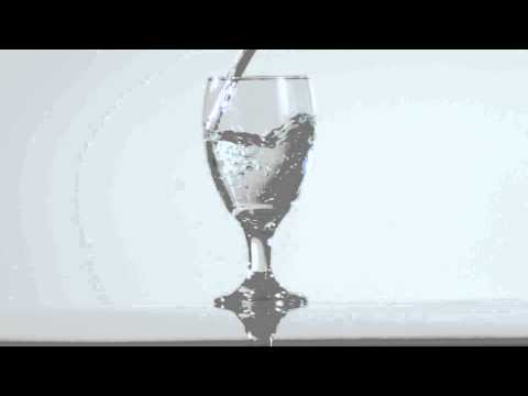 Slow motion footage of clear liquid filling glass