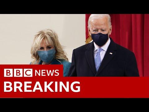 Joe Biden and his wife Jill arrive on the inaugural platform - BBC News