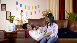 Attractive young kid checking her mom's health using a stethoscope at home