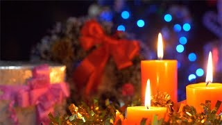 Pan shot of scented candles with wrapped gift boxes with the bokeh effect - Christmas Eve