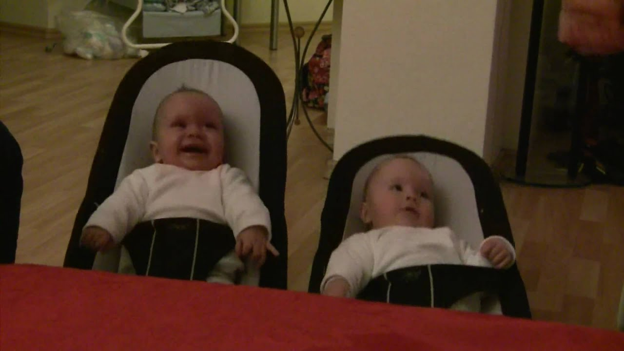 lachende zwillinge in der baby wippe laughing twins with. Black Bedroom Furniture Sets. Home Design Ideas
