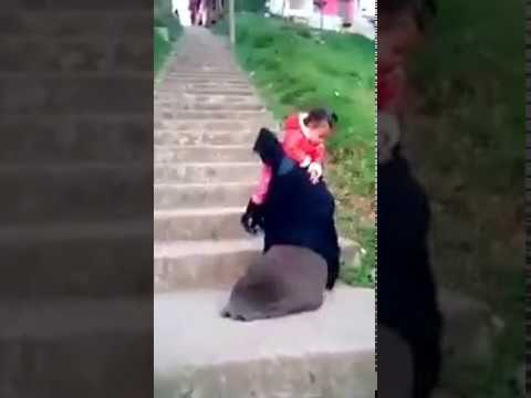 A Father With Amputated Limbs Is Climbing Up The Stairs With His Baby.