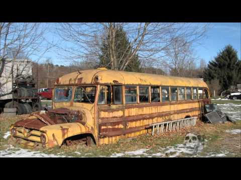 Abandoned vehicles in America: old cars, rusty tractors. Abandoned bus.