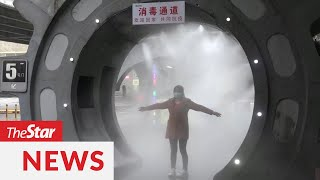 Covid-19: Disinfectant tunnel in China sprays workers