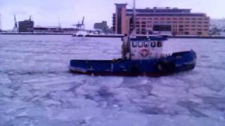 Small tugboat breaking through ice - Sweden