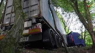 Truck is stuck, is held only by tree and threatens to slip on the slope - firefighting operation