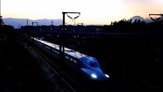 夕方の富士山を背景に疾走する新幹線