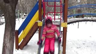 Masha playing on the winter playground Ride on Swing