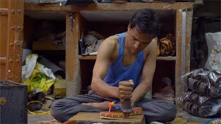 Indian shoemaker beating the soul of the sandal using a tool to paste it well