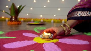 Bokeh shot - Hands of Indian female decorating a colorful rangoli with a burning oil lamp on Diwali