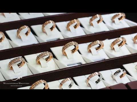 Золотые обручальные кольца с подвижной центральной вставкой и ажурным узором.