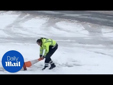 Airport worker tries to clear snow with traffic cone - Daily Mail