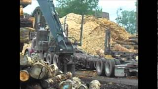 canadian log truck unloading and loading trailer with hitachi forester