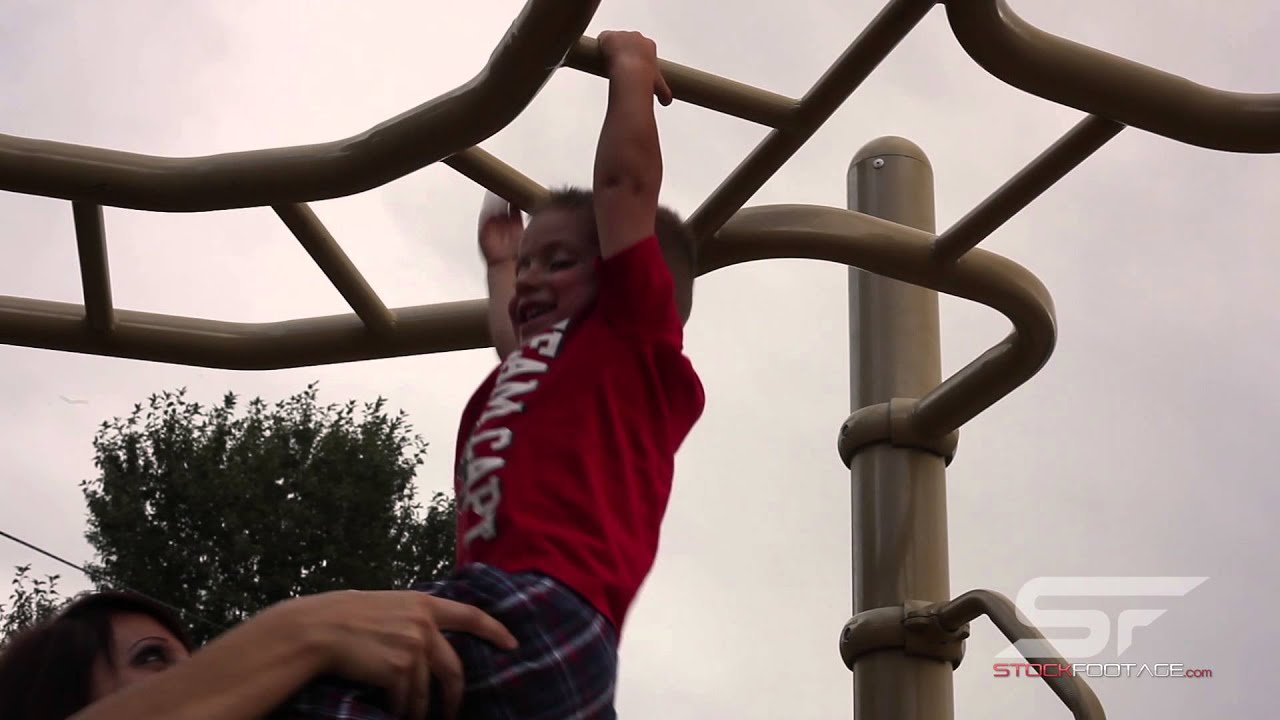 tracking shot of a small boy hanging from monkey bars with help