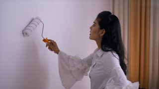 Young Indian woman carefully painting walls in white color with a roller - House Relocation