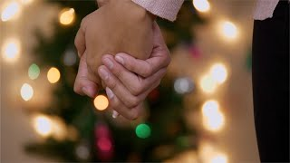 Closeup shot of a couple holding hands with Christmas tree in background with bokeh effect
