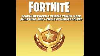 Fortnite Easy Guide Search Between a Vehicle Tower, Rock Sculpture, and a circle of hedges.