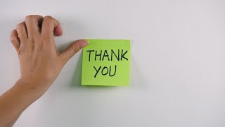 "Closeup shot of woman hands sticking note with ""Thank you"" text on a white wall"
