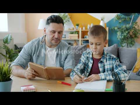 caring-dad-reading-book-to-kid-while-child-drawing-pictures-at-desk-in-apartment