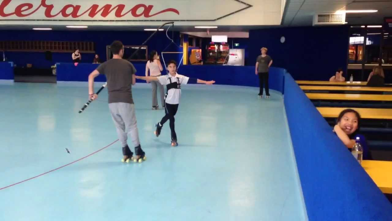 Young Guy Figure Skating With Handheld Jump Harness