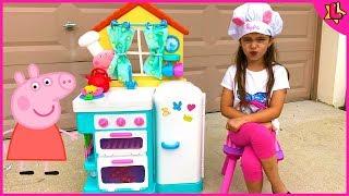 Laurinha finge brincar na cozinha de brinquedo da peppa pig para crianças