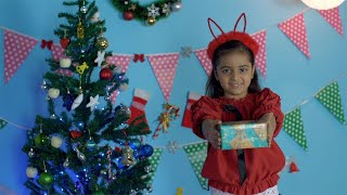 Happy Indian kid offering a Christmas present with a wide smile on her face - casual winter wear