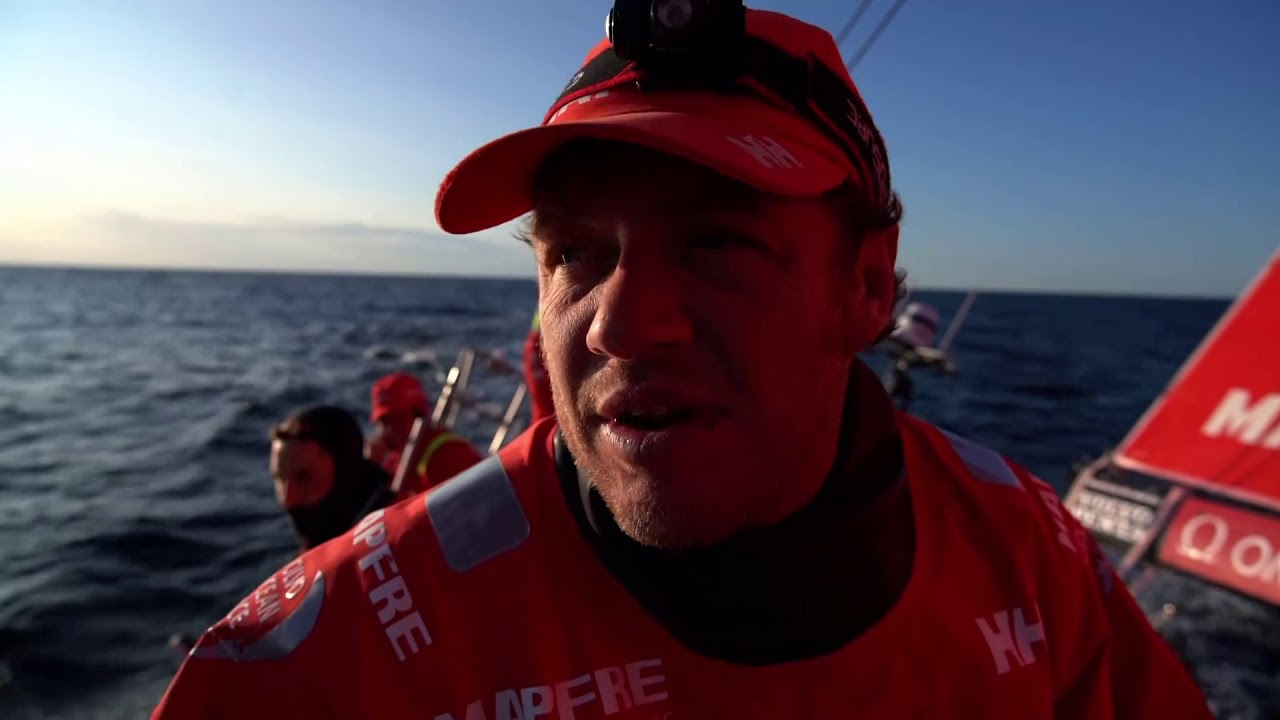 Neti talks in Spanish in the morning light about wind, the fleet, Dongfeng. Repeats in English: Busy night. Pretty tied with Dongfeng. Not too far from the top mark. Last evening had upwind and reaching condiions in medium breeze. Now compression, Dongfeng and us have escaped from the other guys before, now we have to keep in front of them. Loud footage of foredeck work, darkness. Then drifting conditions in the pretty gorgeous sunrise with Dongfeng a quarter mile away. Slomo sailing with Dongfeng behind them. Willy sleeping on the stack forward. Blair, through the hatch, puts his hands up: What?