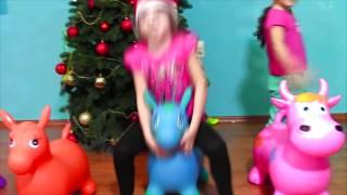 Маша и Аня танцуют и играют возле новогодней елки