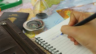 "Closeup shot of woman hands writing the word ""Holidays"" in her travel notebook"