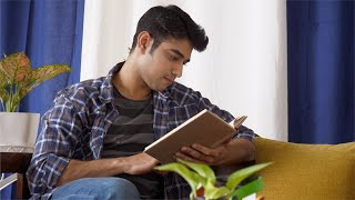 Indian man peacefully reading book sitting comfortably at home