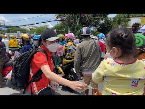 Cô gái cầm xấp tiền phát cho dòng người vạ vật tại chốt chặn, đợi rời Sài Gòn về miền Tây