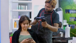 Indian girl having her hair styled by a professional hairdresser in a beauty salon