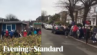 Hundreds queue in cold weather for Covid vaccine at a GP practice in London