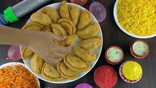 Indian female placing homemade Gujiyas in a white ceramic plate for Holi celebrations