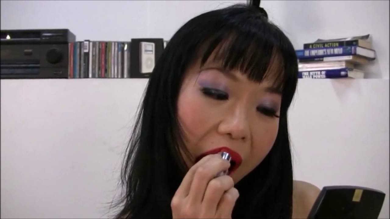 Shemale putting on lipstick