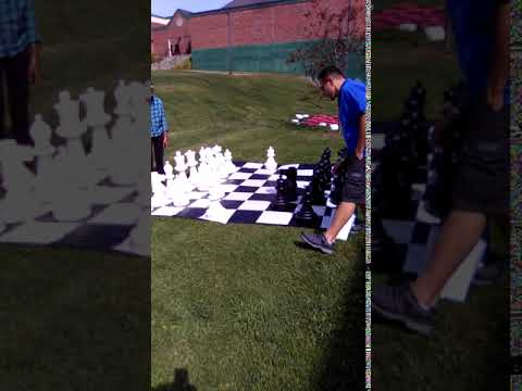 Giant Chess Match with Giant Checkers in the Background