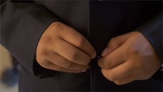 Close-up shot of a man buttoning up his blazer - man dress up