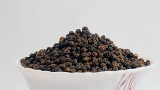 Pan shot of a rotating bowl filled with black pepper (Kaali Mirch - Indian Spice)