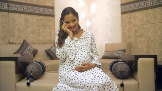 Beautiful pregnant woman caressing her baby bump while talking over a phone call