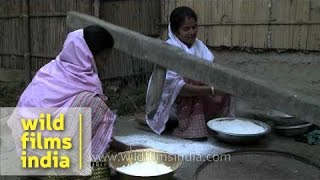 Assamese women pounding rice with wooden rice pounder