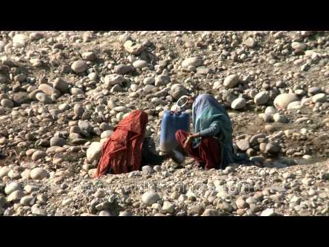 Tribal Gujjar women filtering stream water for drinking in Rajaji National park