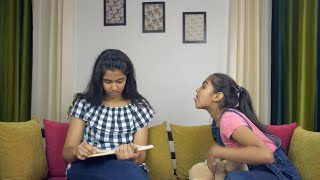 Cute little girl teasing her elder sister while sitting on a couch - living room in the background