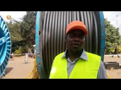 AKS East Africa casual workers and technicians lay power cable through Uhuru Park